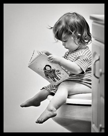 little girl reading in the bathroom